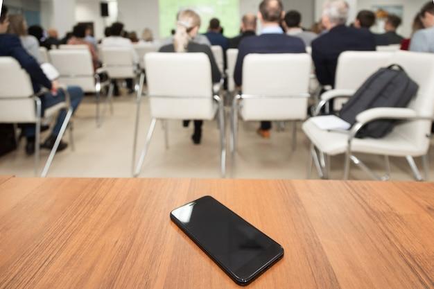 Handy, der auf tabelle des konferenzsaals liegt