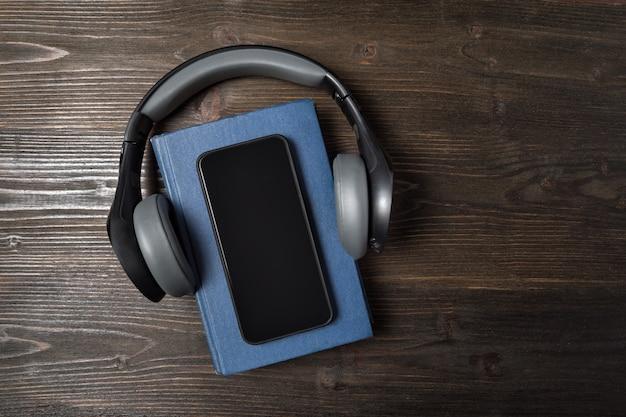 Handy, headphonesi und buch auf dunklem hölzernem hintergrund. hörbuch-konzept. ansicht von oben