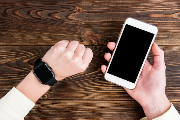 Handy in der hand auf holzbrett