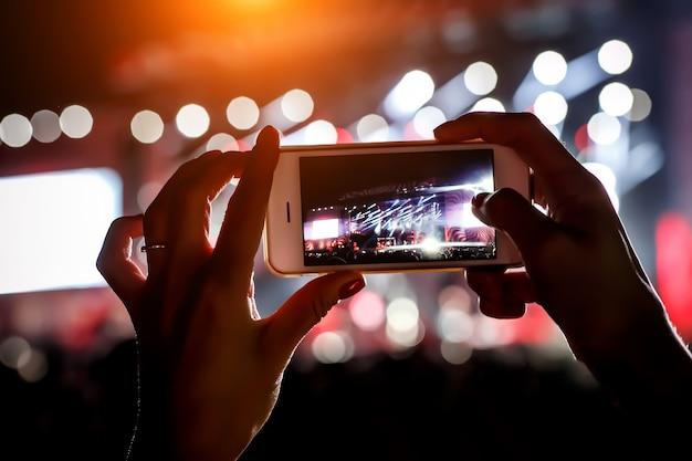 Handy in händen bei einer musikshow. verwenden eines smartphone-konzepts.