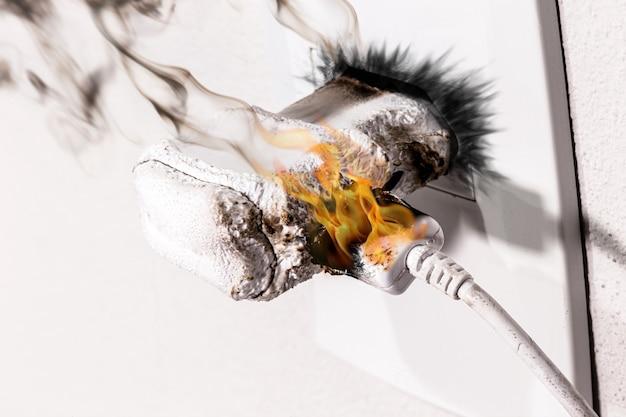 Handy-ladegerät in flammen, kurzschluss in der steckdose