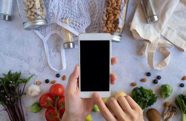 Handy mit dem frischen gemüse auf steinoberfläche. online-lebensmittel- und bio-kaufanwendung für gesunde produkte. essen und kochen rezept oder ernährung diät zählen. flache lage.