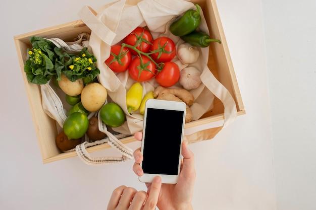 Handy mit der öko-tasche und frischem gemüse in holzkiste. online-anwendung zum einkaufen von lebensmitteln und produkten für biobauern. lebensmittel- und kochrezept oder ernährungszählung.