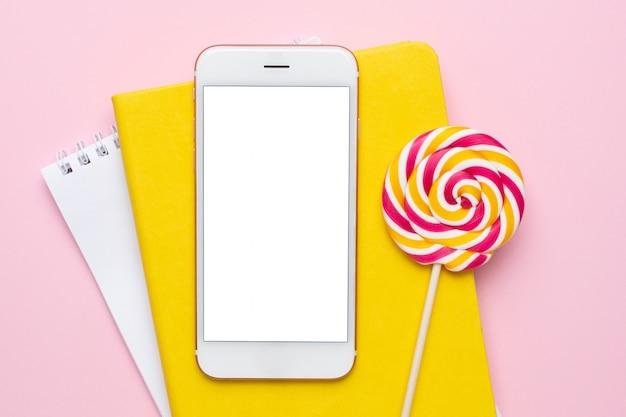 Handy mit einem gelben notizbuch und einem bunten lutscher auf rosa