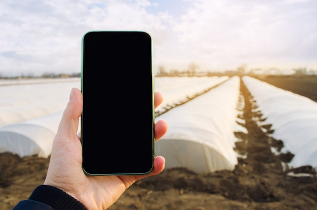 Handy mit einem leeren leeren bildschirm über landwirtschaftlichen gewächshäusern