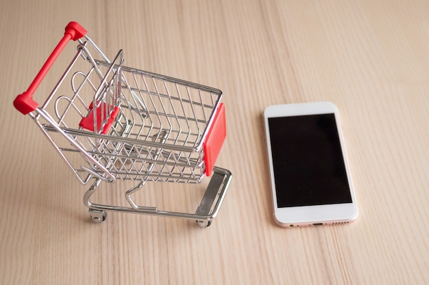 Handy mit einkaufswagen auf holztisch hintergrund einkaufen online-konzept