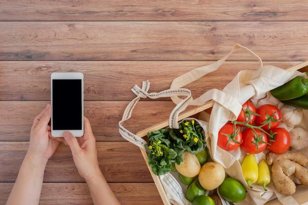 Handy mit frischem gemüse in der holzkiste. online-anwendung zum einkaufen von lebensmitteln und produkten für biobauern. lebensmittel- und kochrezept oder ernährungszählung.