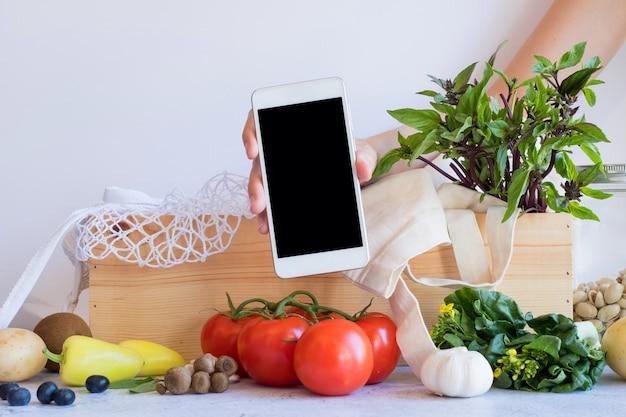 Handy mit frischem gemüse in der holzkiste. online-anwendung zum einkaufen von lebensmitteln und produkten für biobauern. lebensmittel- und kochrezept oder nährstoffzählung.