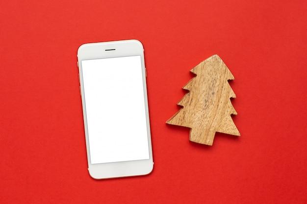 Handy mit hölzernem weihnachtsbaum