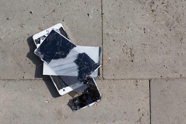 Handy mit kaputtem bildschirm liegt auf dem boden.