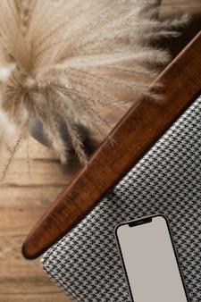 Handy mit leerem bildschirm auf vintage-stuhl. flache lage, minimalistisches blog mit draufsicht, website
