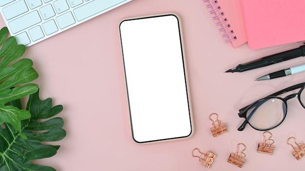 Handy mit leerem bildschirm auf weiblichem arbeitsplatz. flach liegen.