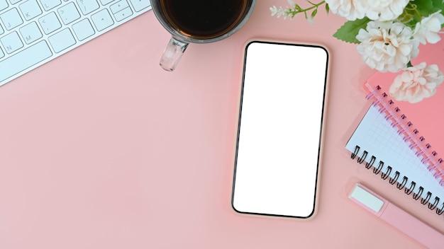 Handy mit leerem bildschirm, kaffeetasse, blumen und notizbuch auf rosafarbenem pastellhintergrund.
