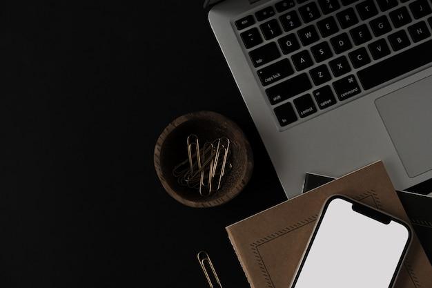 Handy mit leerem bildschirm, laptop, notebook, briefpapier auf schwarz