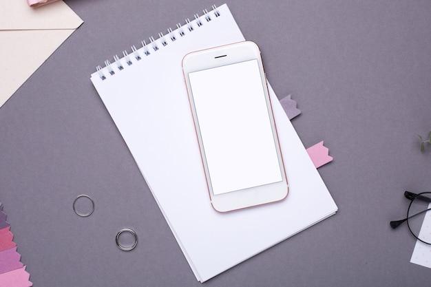 Handy mit leerem bildschirm mit weißem notizblock und stickerei auf grau