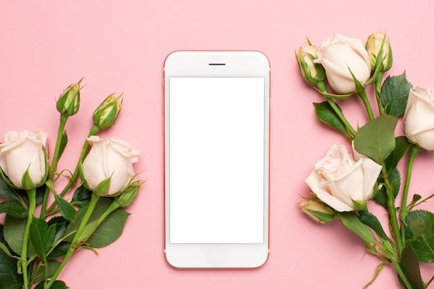 Handy mit rosen blüht auf rosa pastellhintergrund, frauentechnologiekonzept