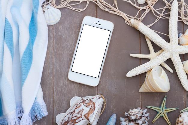 Handy mit strandtuch und muscheln auf weißem hintergrund, kopienraum auf leerem bildschirm