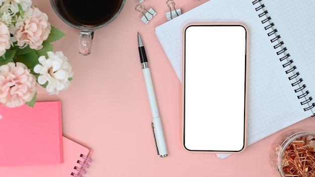 Handy mit weißem bildschirm am weiblichen arbeitsplatz.