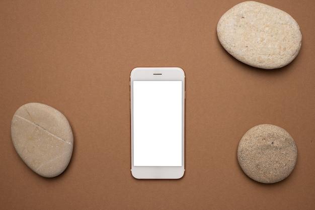 Handy mit weißem bildschirm und stein auf einem hellbraunen.
