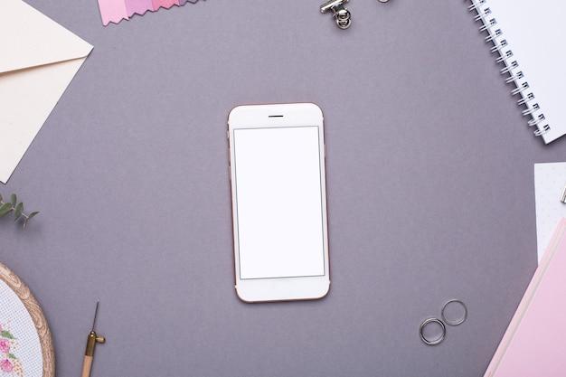 Handy mit weißem notizblock, rosa notizbuch und stickerei auf grau bis