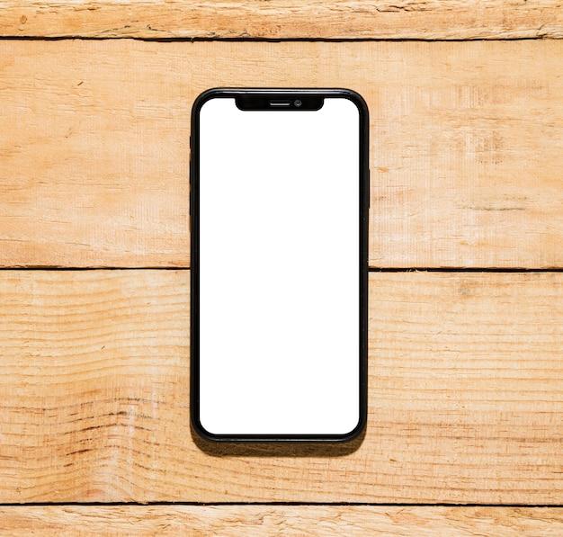 Handy mit weißer bildschirmanzeige auf hölzernem schreibtisch