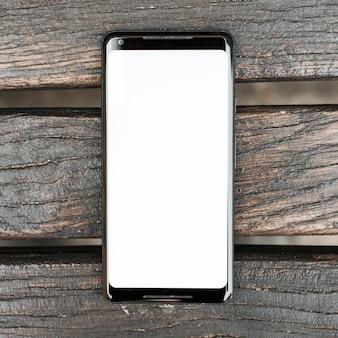 Handy mit weißer Bildschirmanzeige auf hölzerner strukturierter Planke