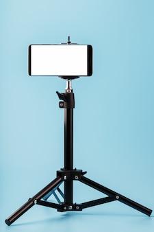 Handy montiert auf einem stativ mit einem weißen display frei für bilder und text, blau isoliert hintergrund.