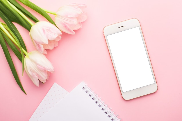 Handy, notebook und frühlingsblume rosa tulpen auf dem rosa