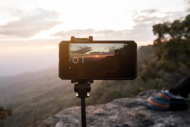 Handy oder smartphone auf stativ mit fotomodus, der ein bild des sonnenuntergangs an der klippe macht: