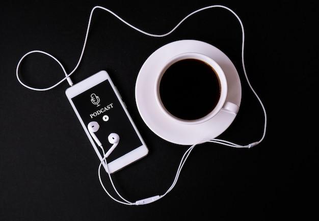 Handy-podcast mit kopfhörern am arbeitsplatz. podcast hören. hörbuch. online-bildung.