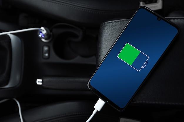 Handy, smartphone, handy ist aufgeladen, akku mit usb-ladegerät im auto aufladen. moderne schwarze autoinnenausstattung.