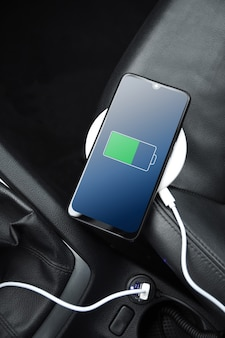 Handy, smartphone, handy wird aufgeladen, akku mit usb-ladegerät im auto aufladen. moderne schwarze autoinnenausstattung.