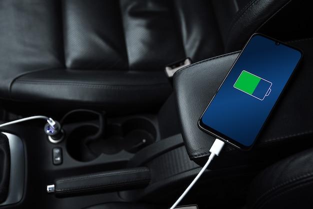 Handy, smartphone, handy wird aufgeladen, akku mit usb-ladegerät im auto aufladen. modernes schwarzes autointerieur