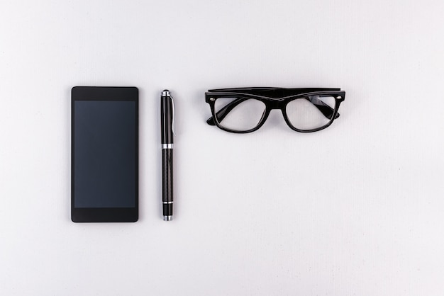 Handy, stift und brille auf weißer oberfläche