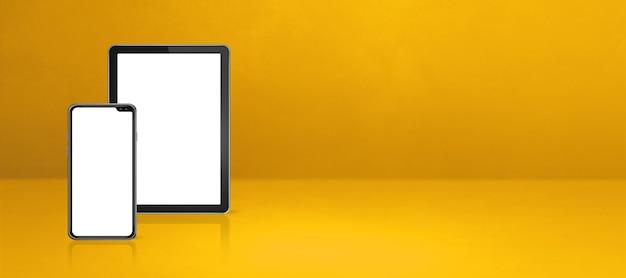 Handy und digitaler tablet-pc auf gelbem schreibtisch