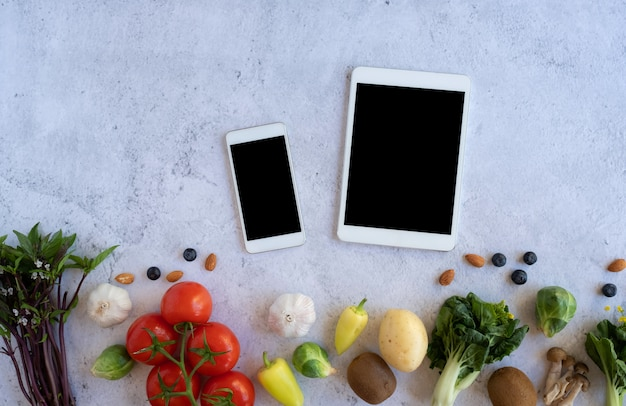 Handy und digitales tablet mit frischem gemüse auf steinoberfläche. online-lebensmittel- und bio-kaufanwendung für gesunde produkte. lebensmittel- und kochrezept oder ernährungsdiät zählen.
