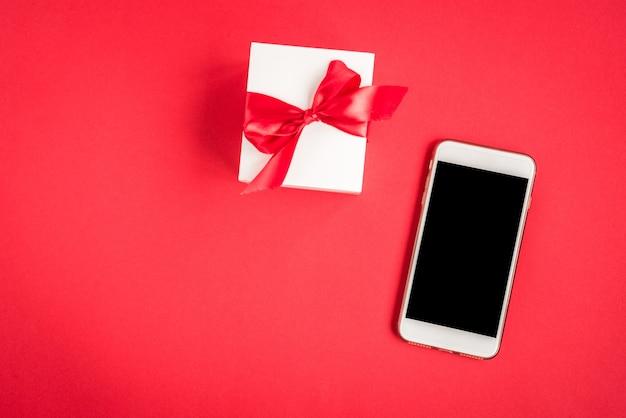 Handy und geschenkbox auf rot.