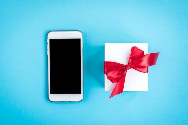 Handy und geschenkbox mit roter schleife auf blau.