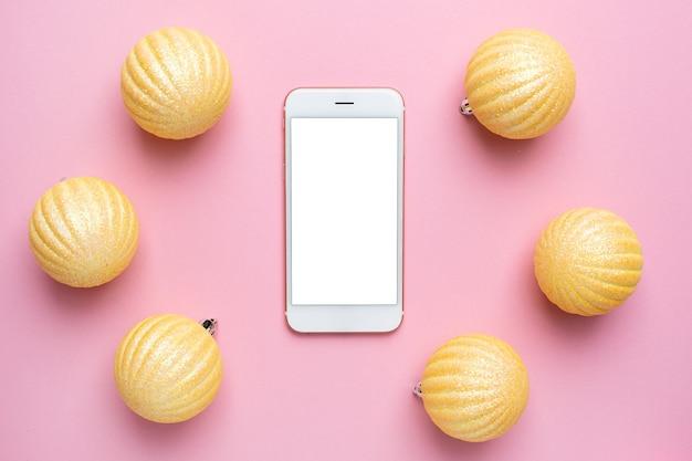 Handy und glänzende goldkugeln auf einem rosa isoliert