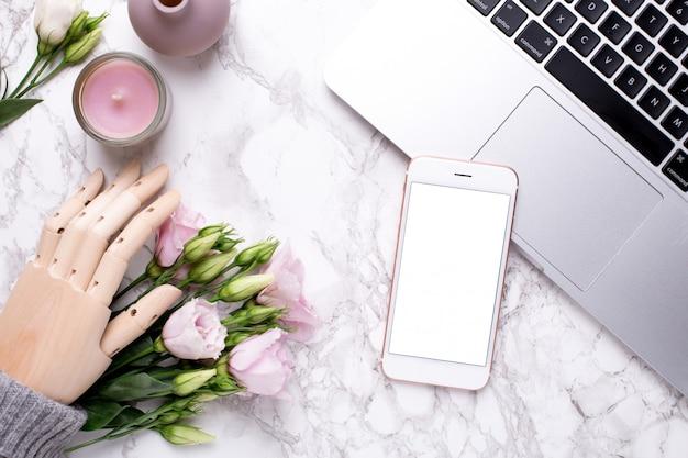 Handy und hölzerne hand mit rosa blumen auf marmor