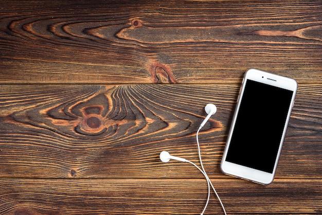 Handy und kopfhörer auf holzbrett