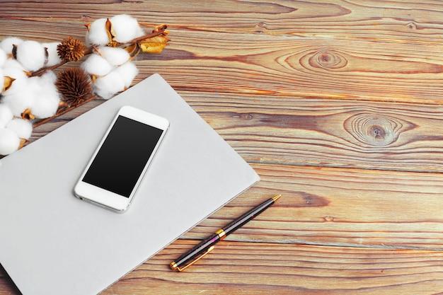 Handy- und niederlassungsbaumwollblume auf dem tisch. ansicht von oben.