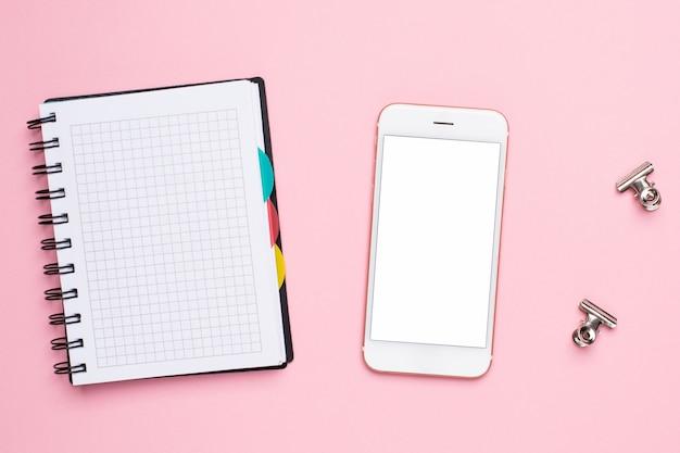 Handy und notizbuch in einem käfig auf einem rosa hintergrund