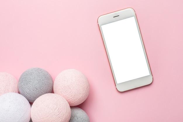Handy und rosa, graue und weiße kugeln girlande auf einem pastell