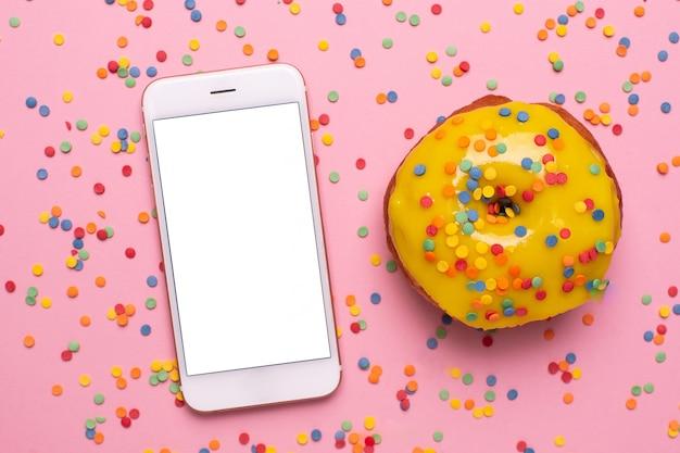 Handy und süßer gelber donut auf einer rosa hintergrundebenenlage