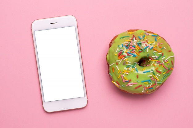 Handy und süßer grüner donut auf einer rosa hintergrundebenenlage