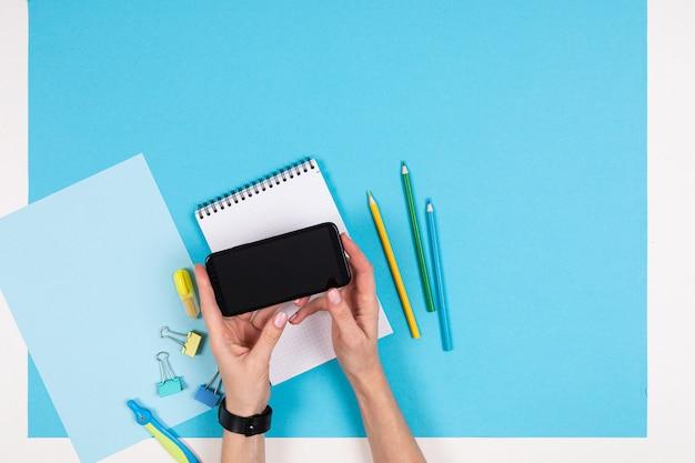 Handy und verschiedene schreibwaren isoliert auf weiß und blau