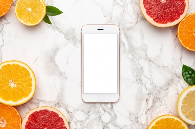Handy und zitrusfrüchte auf marmoroberfläche, frucht-flatlay, sommerliche minimalkomposition mit grapefruit, zitrone, mandarine und orange