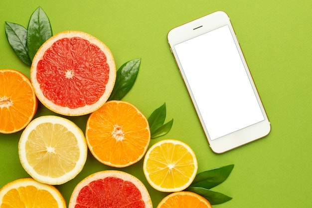 Handy und zitrusfrüchte, technologie und obst flatlay, sommerliche minimalkomposition mit grapefruit, zitrone, mandarine und orange