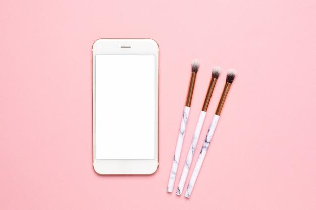 Handy verspotten und schönheit bilden bürsten auf einer draufsicht des rosa hintergrundes